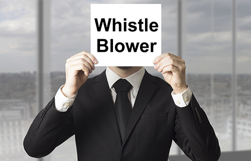 Business man holding a sign in front of his face that says whistle blower