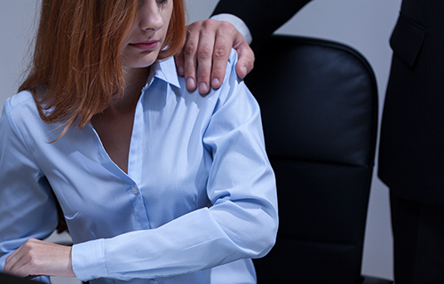 Business woman feeling uncomfortable because of business man's hand on her shoulder